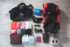 Mochila y equipaje listo para viajar a Tailandia con ropa de algodón y lino cómoda, sandalias, pasaporte y cámara de fotos
